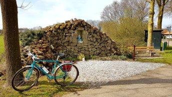 Mijn fiets bij een Maria-grot gemaakt van resten van de fundering van een Nederlandse lege barak uit WO 2