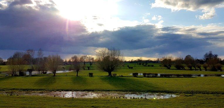 De dijk langs de IJssel was aan beide zijden mooi, aan de IJssel kant blauwe lucht, aan de andere kant vol met regen...